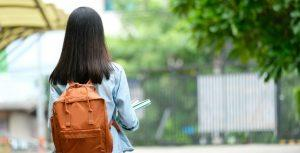 Girl standing infront of school gates with backpack and books in hand